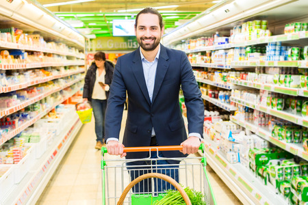 Man driving shopping cart while grocery shopping in supermarket  Stock Photo