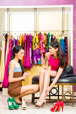 choosing clothes: Asian young sales lady offering shoes to woman in fashion store