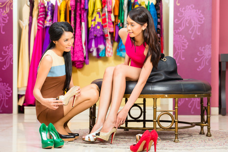 comprando zapatos: Señora asiática de ventas joven que ofrece zapatos para mujer en la tienda de moda