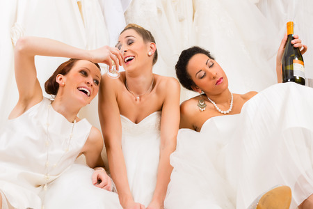 Brides drinking too much in wedding shop or store photo