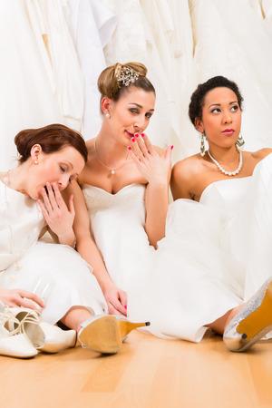 Brides drinking too much champagne in wedding shop photo