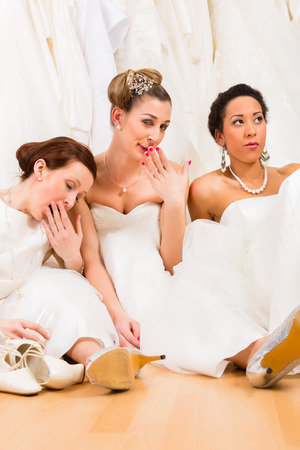 tipsy: Brides drinking too much champagne in wedding shop Stock Photo