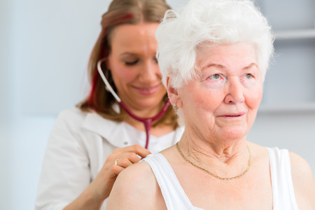 auscultate: Female doctor auscultate breath and lungs of pensioner with stethoscope in surgery  Stock Photo