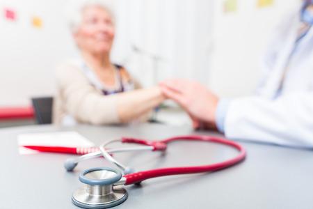 Arts zitten met een gepensioneerde in de chirurgie spreekuur op het bureau Stockfoto