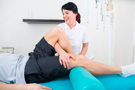 Patient at the physiotherapy doing physical exercises with his therapist photo