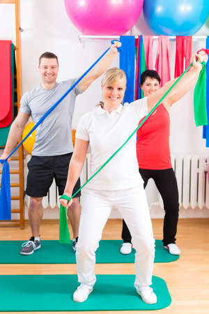 rubber bands: Patients at the physiotherapy doing physical exercises with therapist