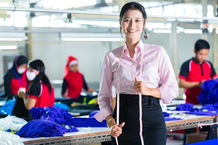Weiblich indonesischen Schneider, Schneiderin oder Designerin steht stolz in einem asiatischen Textilfabrik, ist es ihr Arbeitsplatz Standard-Bild