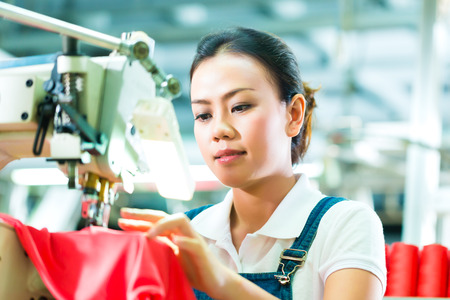 chinese woman: Seamstress or worker in a chinese factory sewing with a industrial sewing machine, she is very accurate