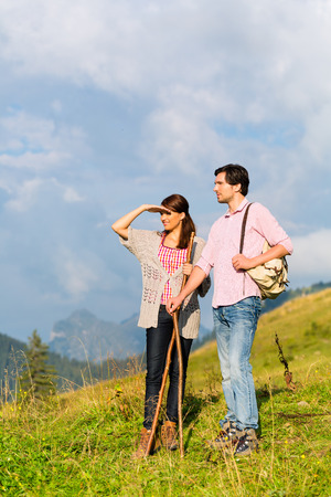 Couple on fitness hiking vacation on mountain summit or alpine grassland in the Alps Stock Photo