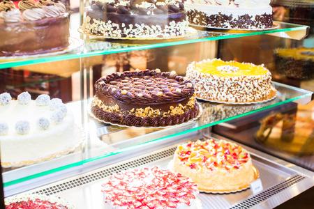 Patisserie glazen display met een selectie van de crème of fruit cake Stockfoto