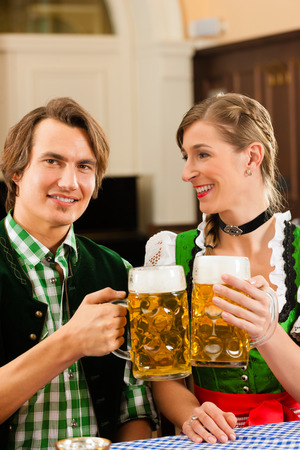 steins: Young couple in traditional Bavarian Tracht in restaurant or pub with beer Stock Photo