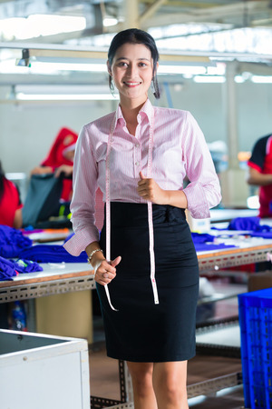 Female Indonesian tailor, dressmaker or designer standing proudly in an Asian textile factory, it is her workplace photo