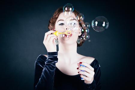 bursting: Girl making soap bubbles in front of dark