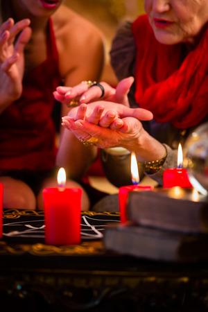 adivino: Mujer adivino o esotérica Oracle, ve en el futuro mediante la lectura de manos durante una sesión de espiritismo para interpretarlos y para responder a las preguntas Foto de archivo