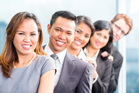Portrait of smiling Asian business people standing in row photo