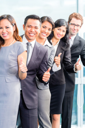 Portrait of Asian businesspeople showing thumbs up photo