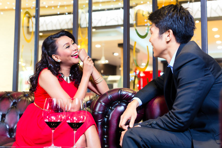 view of an elegant red couch: Young Asian couple sitting in a bar and chatting