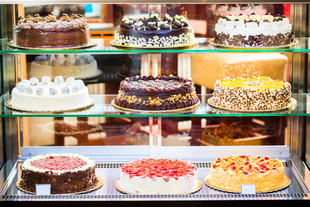 Patisserie glazen display met een selectie van de crème of fruit cake