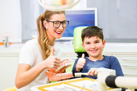 tooth cleaning: Female dentist explaining boy cleaning tooth with toothbrush on model