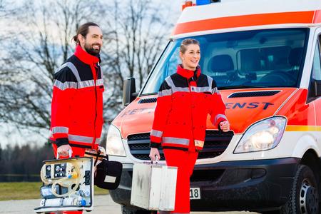 Médico de emergencia y la enfermera de pie delante de la ambulancia