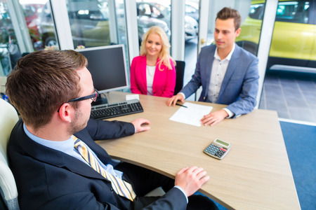 auto leasing: Couple buying car at dealership and negotiating price with salesman Stock Photo