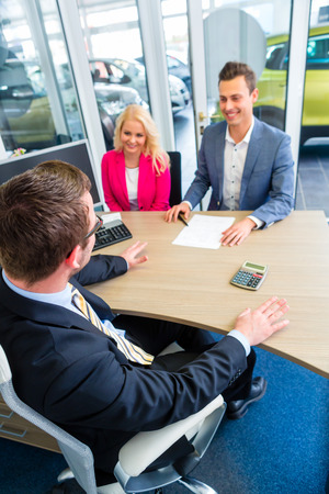 car sales: Couple buying car at dealership and negotiating price with salesman Stock Photo
