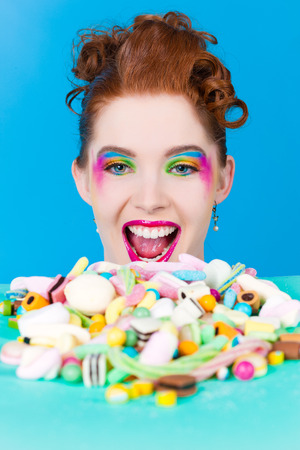 sweet tooth: Young woman with many unhealthy sweets or candy in Studio, she have a sweet tooth Stock Photo