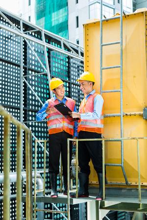 supervisión: Trabajadores de la construcción de Indonesia de Asia con el casco y el chaleco de seguridad en un edificio o complejo industrial en Asia