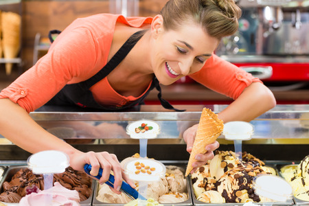 parlor: Young saleswoman in an ice cream parlor takes a scoop of ice cream