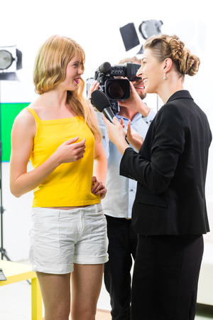 interviewing: Reporter and cameraman film shoot actress interview on film set for TV or  Television