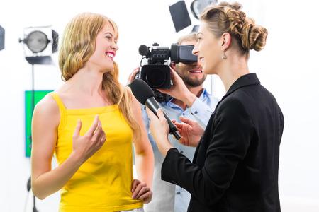 hombre disparando: Periodista y camarógrafo rodaje entrevista la actriz en el set de película para la televisión o la televisión
