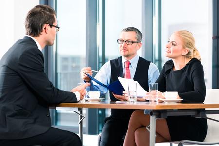 entrevista de trabajo: De negocios - hombre joven en una entrevista de trabajo, las manos sobre los documentos de solicitud al jefe y su asistente femenina en su oficina