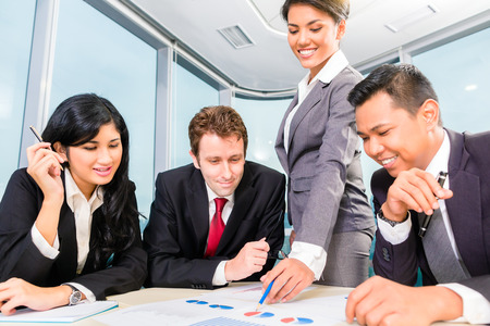 Asian Businesspeople anaylzing graph in office photo
