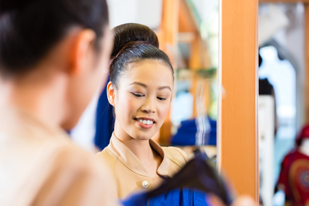 Asian Woman shopping in boutique or fashion store looking at herself in mirror photo