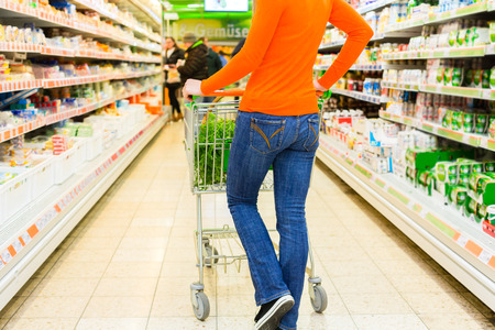 woman shopping cart: Woman driving shopping cart while grocery shopping in supermarket