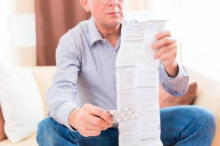 Viejo hombre que lee prospecto medicamento en casa con gafas Foto de archivo