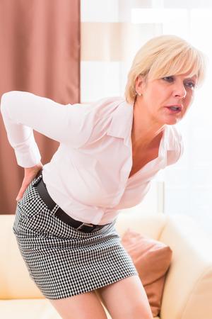 nervios: Anciana sosteniendo la espalda a causa de la lumbalgia Foto de archivo