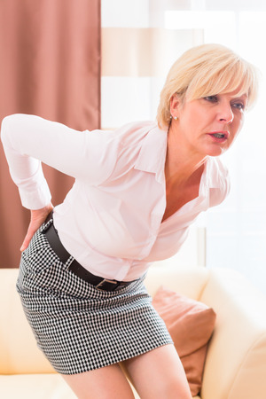 lower back pain: Old woman holding back because of lumbago