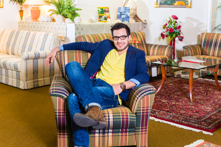 furnish: Young man testing and buying armchair in furniture store Stock Photo