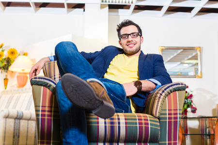 Young man testing and buying armchair in furniture store Stock Photo
