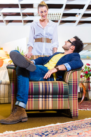 Young couple selecting together armchair in furniture store  photo