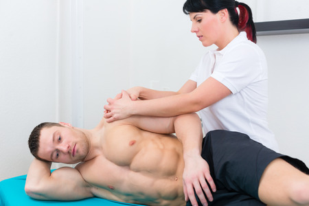 physical therapist: Patient at the physiotherapy doing physical exercises with his therapist