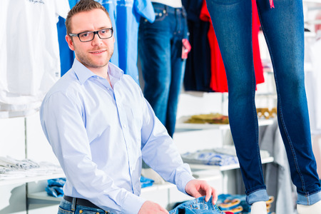 Handsome Man buying blue jeans in shop or store photo