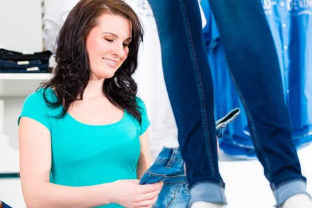 Woman buying fashion blue jeans in shop or store photo