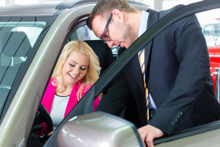 test drive: Woman buying new car in auto dealership