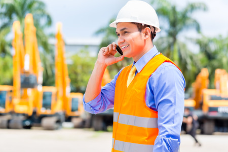 Asian foreman telephoning with mobile phone of building site or mining or rental company Stock Photo