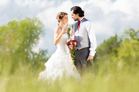 marrying: Wedding bride and groom in a meadow, with bridal bouquet, champagne, and glasses Stock Photo