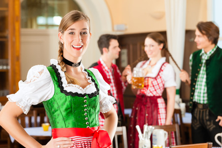clique: Young people in traditional Bavarian Tracht in restaurant or pub, one woman is standing in front, the group in the background