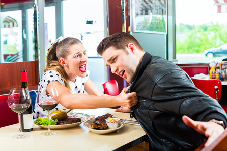 angry couple: Young couple eating fast food and drinking red wine in a American retro fast food diner argues