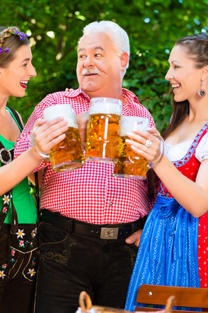 In Beer garden - friends in Tracht, Dirndl and Lederhosen drinking a fresh beer in Bavaria, Germany Stock Photo - 29284532